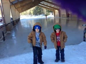 The boys standing by the outdoor ice rink.